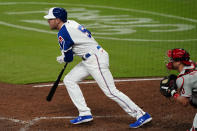 Atlanta Braves first baseman Freddie Freeman (5) drives in a run with a ground ball as Philadelphia Phillies catcher J.T. Realmuto (10) looks on in the seventh inning of a baseball game Saturday, April 10, 2021, in Atlanta. (AP Photo/John Bazemore)