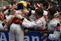 FILE - In this Sunday, April 17, 2011 file photo, McLaren Formula One driver Lewis Hamilton of Britain, with yellow helmet, celebrates with his crews after winning the Chinese Formula One Grand Prix in Shanghai, China. British driver Lewis Hamilton made Formula One history on Sunday, Oct. 25, 2020 winning the Portuguese Grand Prix for a 92nd win to move one ahead of German great Michael Schumacher. (AP Photo/Eugene Hoshiko, file)