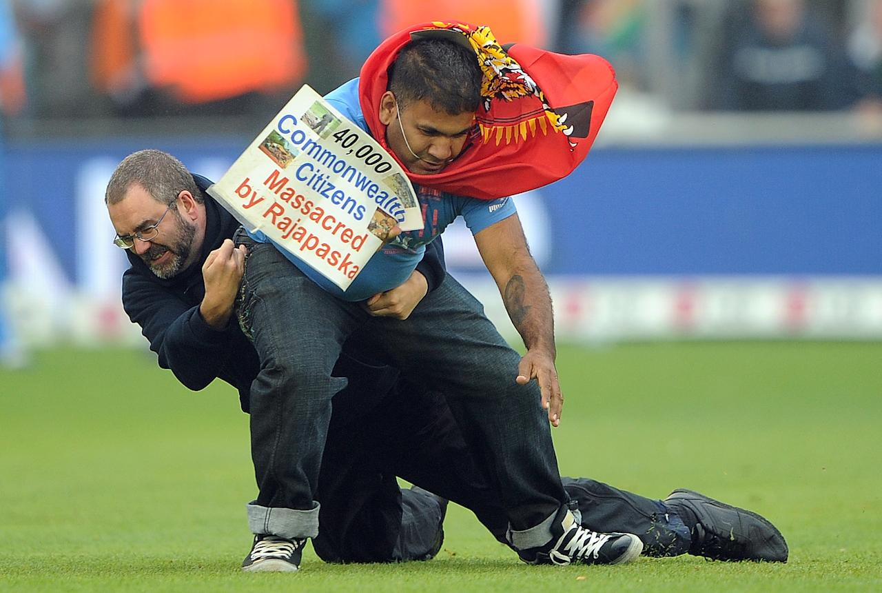 A pitch invader is tackled by a steward during the 2013 ICC Champions Trophy semi-final cricket match between India and Sri Lanka at the Cardiff Wales Stadium in Cardiff, south Wales, on June 20, 2013. AFP PHOTO/ANDREW YATES  == RESTRICTED TO EDITORIAL USE ==
