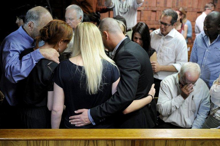 "The father of South African Olympic sprinter Oscar Pistorius, Henke (right), reacts as relatives comfort each other on February 19, 2013 after his bail hearing in Pretoria was adjourned. ""Blade Runner"" Oscar Pistorius returned to court Wednesday to hear explosive allegations that he fought ""non-stop"" with his slain girlfriend Reeva Steenkamp on the night of her killing"