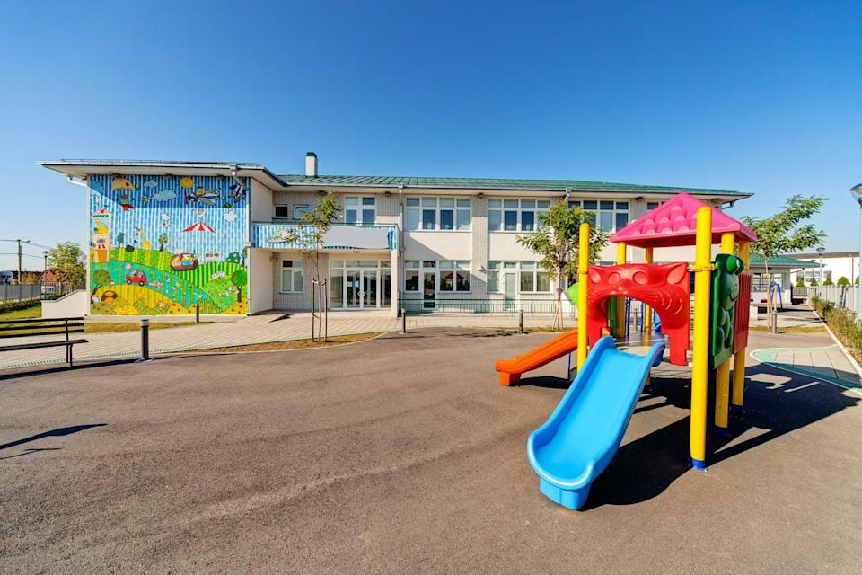 A playground with a blue slide for young children seen outside a school building.
