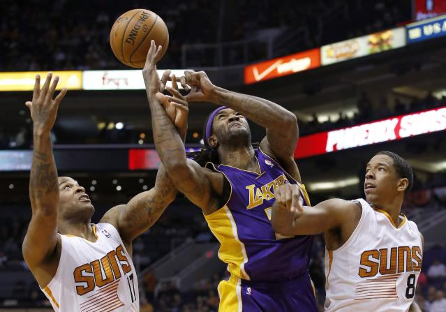 Los Angeles Lakers' Jordan Hill, middle, loses the ball as Phoenix Suns' P.J. Tucker, left, tips it away while Suns' Channing Frye (8) defends during the first half of an NBA basketball game Wednesday, Jan. 15, 2014, in Phoenix. (AP Photo/Ross D. Franklin)