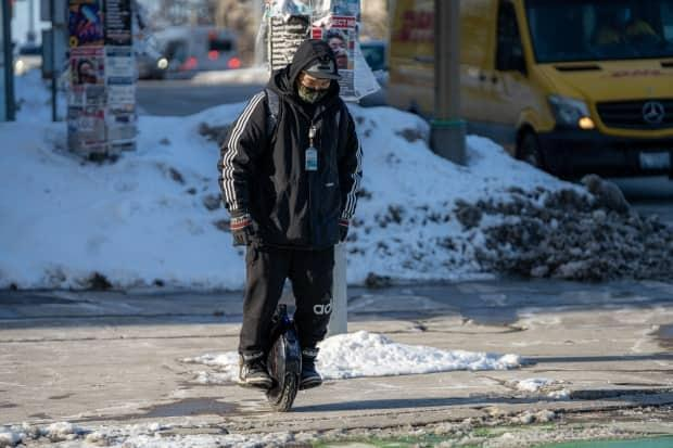An electric unicycle rider wears a mask on the edge of a sidewalk and bike lane in Ottawa in early March 2021. (Andrew Lee/CBC - image credit)