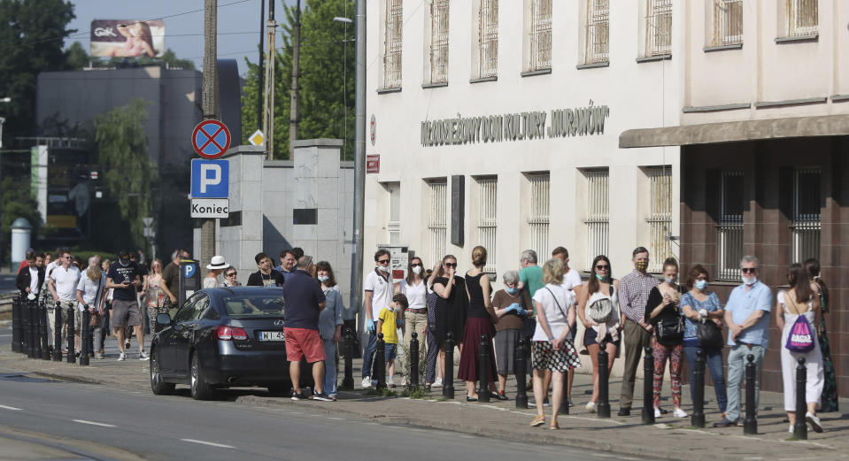 People wearing protective face masks observe mandatory social distancing against the spread of the coronavirus as they wait in line to cast their votes in Poland's presidential election. The election will test the popularity of incumbent President Andrzej Duda who is seeking a second term and of the conservative ruling party that backs him, in Warsaw, Poland, Sunday, June 28, 2020. (AP Photo/Czarek Sokolowski)