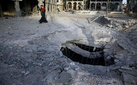 A Syrian woman walks past damaged buildings in Douma, in the eastern Damascus suburb of Ghouta