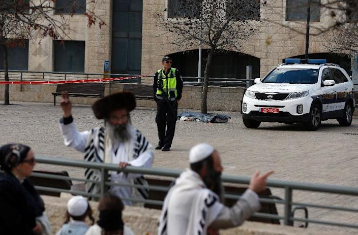 An ultra-Orthodox Jewish man holds up a V-sign as an Israeli policeman stands next to the body a Palestinian assailant who was shot dead near Jerusalem's Old City following a reported attack on December 26, 2015 (AFP Photo/Ahmad Gharabli)