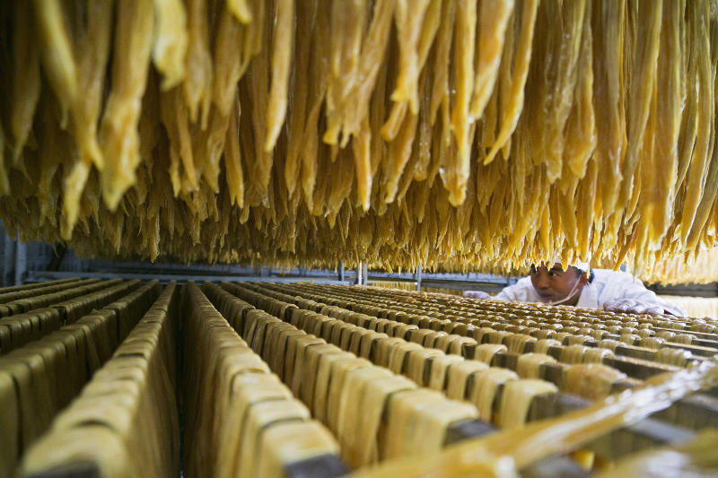 In this Jan. 10, 2019, photo released by Xinhua News Agency, a worker checks on a soybean food at a processing factory in Xiaotun Township of Dafang County in Bijie, southwest China's Guizhou Province. China's trade growth slowed in 2018 as a tariff battle with Washington heated up and global consumer demand weakened. Exports rose 7.1 percent, customs data showed Monday, Jan. 14, 2019 down from the 7.9 percent reported earlier for 2017. Import growth declined to 12.9 percent from the previous year's 15.9 percent. (Luo Dafu/Xinhua via AP)