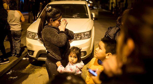 A woman prays in the street after an 8.3 magnitude quake in Chile. Photo: Reuters