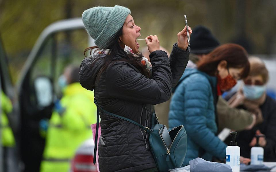 People take part in coronavirus surge testing on Clapham Common, south London. Thousands of residents have queued up to take coronavirus tests at additional facilities set up after new cases of the South African variant were found in two south London boroughs. 44 confirmed cases of the variant have been found in Lambeth and Wandsworth, with a further 30 probable cases identified - PA