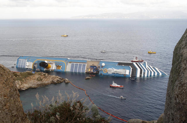 FILE - In this , Sunday, Jan. 22, 2012 file photo, the cruise ship Costa Concordia lies on its side off the Tuscan island of Giglio, Italy. Costa Crociere SpA says work to remove the capsized Costa Concordia cruise ship from its rocky perch off Tuscany will begin early next month and is expected to take 12 months. Costa said in a statement Saturday, April 21, 2012, the U.S.-owned company Titan Salvage won the bid to remove the ship, which struck rocks off the tourist-dependent island of Giglio on Jan. 13, when the captain made an unauthorized maneuver too close to shore. (AP Photo/Pier Paolo Cito, File)