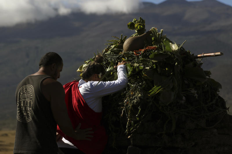 FILE - In this July 14, 2019 file photo, native Hawaiian activists pray at the base of Hawaii's Mauna Kea pictured in background. A leading Spanish official said Monday Aug. 5, 2019, that the consortium pushing to build a giant telescope in Hawaii amid continued protests by locals is planning to ask for a building permit for an alternative site in Spain's Canary Islands. The notification comes as Native Hawaiian protesters enter the fourth week of blocking construction of the telescope on a mountain they consider sacred. (AP Photo/Caleb Jones, File)