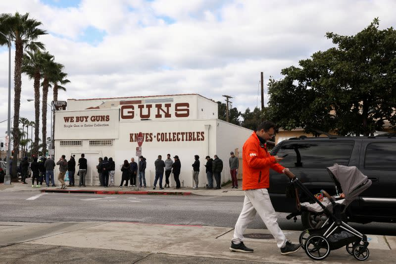FILE PHOTO: A pedestrian pushes a stroller as people wait in line outside to buy supplies at the Martin B. Retting, Inc. gun store amid fears of the global growth of coronavirus cases, in Culver City
