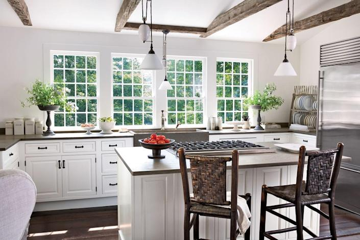 """<p>This kitchen feels refreshingly open and airy, thanks to a white-and-gray palette, the absence of upper cabinets, and that stunning wall of windows! The homeowner added a medley of distinctive pulley lights from Europe and an antique dish rack dating back to 1865 that was, she says, """"the perfect weathered gray.""""</p>"""