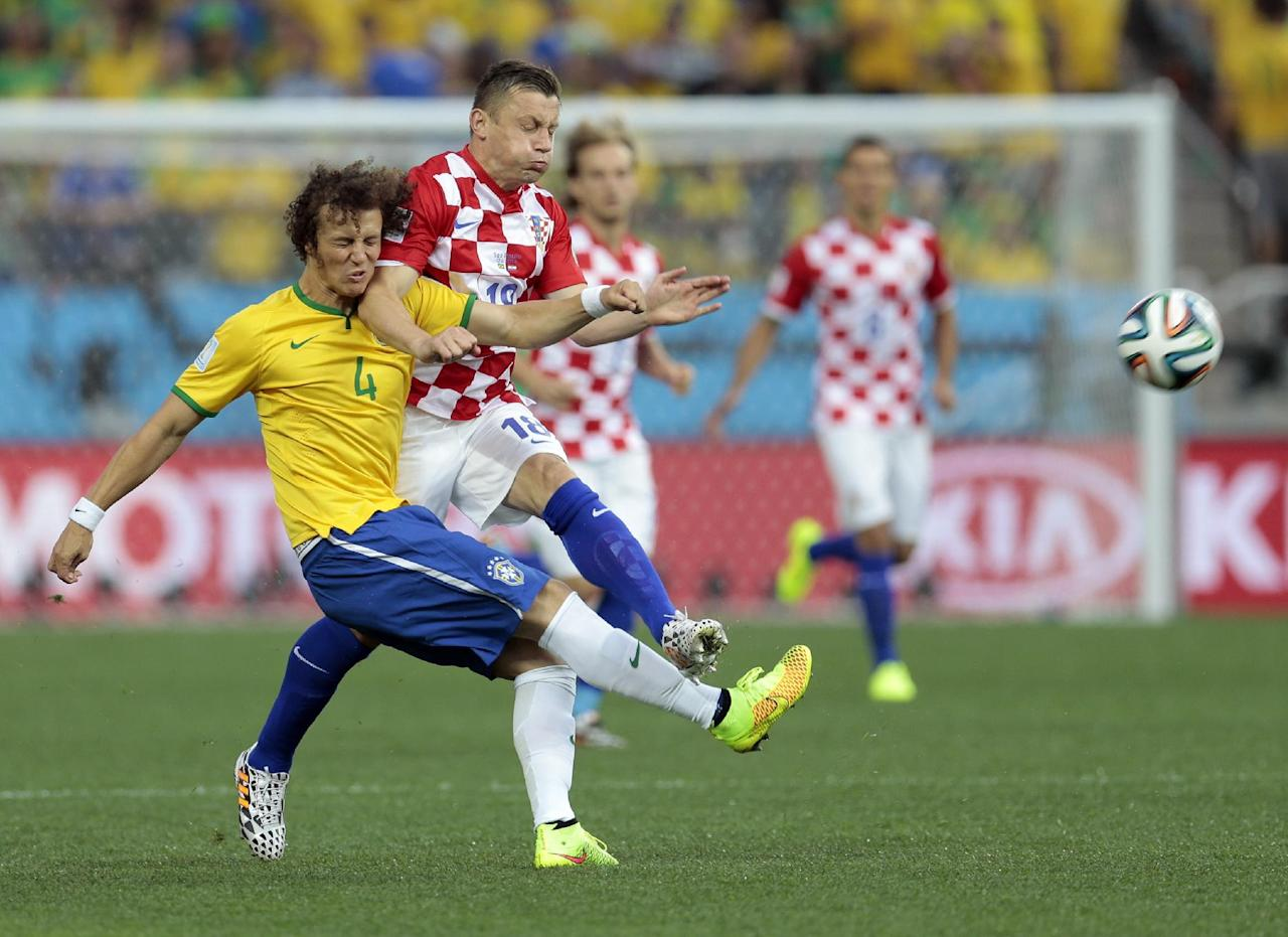 Brazil's David Luiz collides with Chile's Gonzalo Jara during the group A World Cup soccer match between Brazil and Croatia, the opening game of the tournament, in the Itaquerao Stadium in Sao Paulo, Brazil, Thursday, June 12, 2014.  (AP Photo/Ivan Sekretarev)