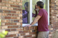 FILE - Jack Campise talks with his mother, Beverly Kearns, through her apartment window at the Kimberly Hall North nursing home, Thursday, May 14, 2020 in Windsor, Conn. A focus on the elderly at the start of the nation's vaccination campaign helped protect nursing homes that were ravaged at the height of the U.S. coronavirus outbreak, but they are far from in the clear. New outbreaks, often traced to infected staff members, are still occurring in long-term care centers across the country, causing continued havoc for visitation policies.(AP Photo/Chris Ehrmann)