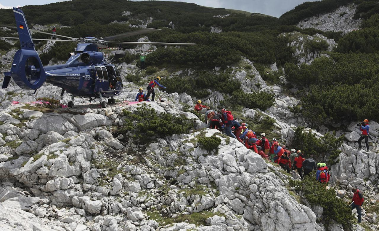 Photo provided by mountain rescue service Bavaria shows rescuers carrying the stretcher with injured German cave researcher Johann Westhauser to helicopter after pulling him out of the country's deepest cavern near Berchtesgaden at the German-Austrian border Thursday, June 19, 2014. The final stretch marked the end of a spectacular rescue operation that lasted nearly a week. Westhauser sustained head injuries in a rock fall June 8 while nearly 1,000 meters (3,280 feet) underground in the Riesending cave system. (AP Photo/Bergwacht Bayern)