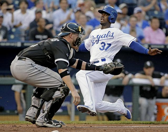 Kansas City Royals' Pedro Ciriaco (37) slides home past Chicago White Sox catcher Tyler Flowers to score on a single by Norichika Aoki during the third inning of a baseball game Wednesday, May 21, 2014, in Kansas City, Mo. (AP Photo/Charlie Riedel)