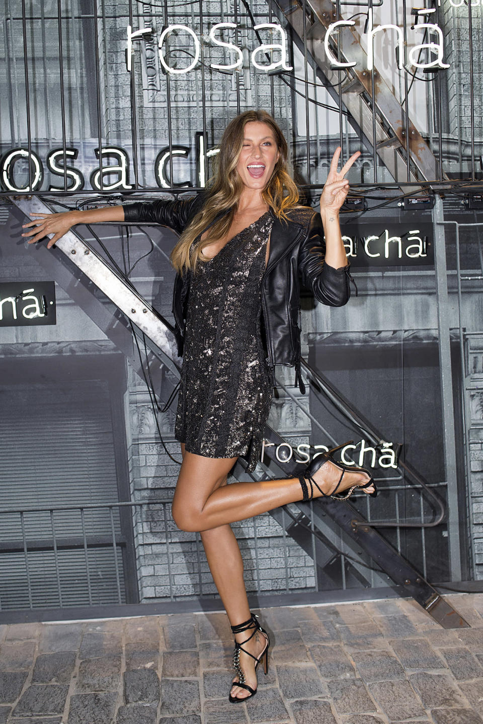 <p>Gisele does a flirty leg pop along with flashing the peace sign at the Rosa Chá event in São Paulo. (Photo: Getty Images) </p>