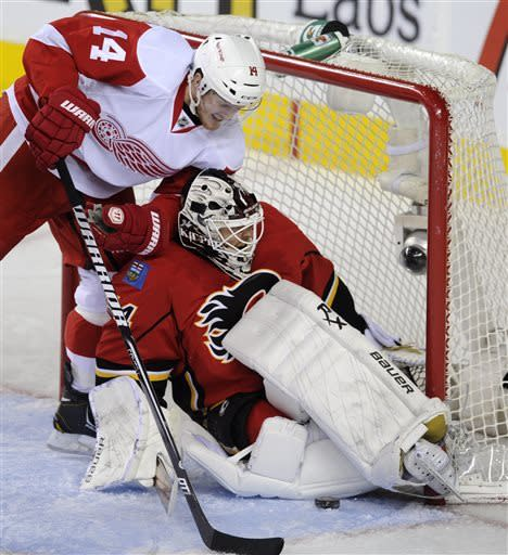 Calgary Flames goalie Miikka Kiprusoff, right, of Finland, makes a save as Detroit Red Wings' Gustav Nyquist, of Sweden, pressures during the second period of their NHL hockey game in Calgary, Alberta, Wednesday, April 17, 2013. (AP Photo/The Canadian Press, Larry MacDougal)