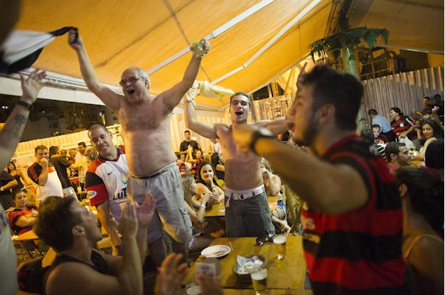 In this April 13, 2014 photo, fans of the Flamengo soccer team celebrate in a bar after their team won the Rio de Janeiro state championship against Vasco in Rio de Janeiro, Brazil. The upcoming World Cup in Brazil will be the first in the South American nation since 1950. (AP Photo/Leo Correa)