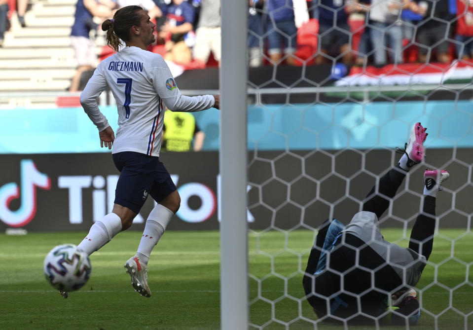 France's Antoine Griezmann, left, celebrates after scoring his sides first goal past Hungary's goalkeeper Peter Gulacsi during the Euro 2020 soccer championship group F match between Hungary and France at the Ferenc Puskas stadium in Budapest, Hungary Saturday, June 19, 2021. (Tibor Illyes/Pool via AP)