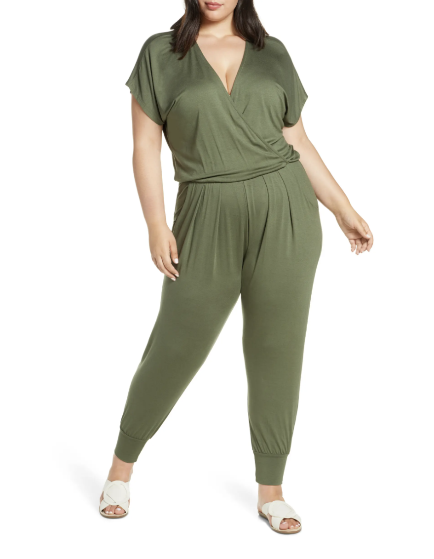 plus size model in v-neck olive green jumpsuit and white sandals