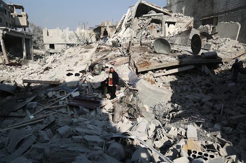 Civilians look for victims under the rubble following a reported air strike on the rebel-held town of Hammuriyeh in Eastern Ghouta on January 9, 2018