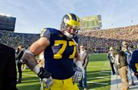 Michigan offensive lineman Taylor Lewan (77) walks off the field in dejection after an NCAA college football game against Ohio State in Ann Arbor, Mich., Saturday, Nov. 30, 2013. Ohio State won 42-41. (AP Photo/Tony Ding)