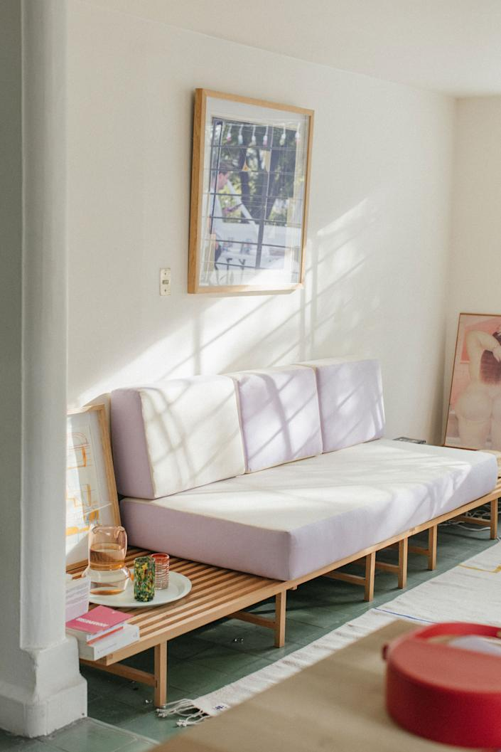 "<div class=""caption""> ""When it came time to furnish the apartment, we wanted to make the most of the space and most of the vintage or new sofas were not suitable,"" says Charles. So, the couple took inspiration from a Charlotte Perriand exhibition and commissioned a friend, <a href=""https://www.instagram.com/franprices/?hl=en"" rel=""nofollow noopener"" target=""_blank"" data-ylk=""slk:Lucyle Wagner,"" class=""link rapid-noclick-resp"">Lucyle Wagner,</a> to craft the piece. ""To give a Mexican touch, we chose the color Lila. Indeed, at the beginning of each spring, the jacaranda trees bloom and flood Mexico City with their purple flowers."" </div>"