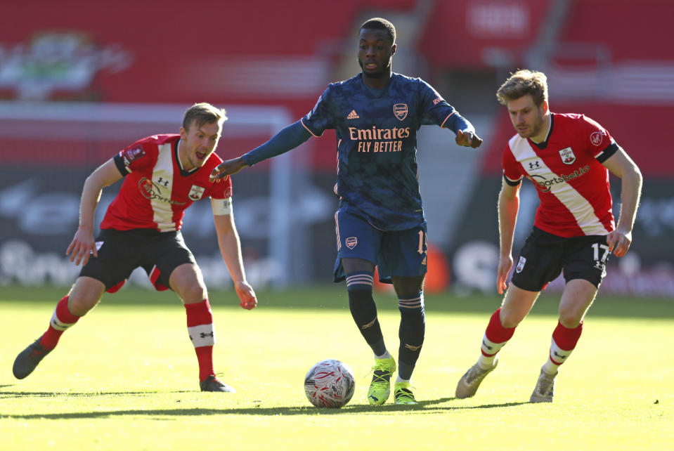 Arsenal's Nicolas Pepe, center, battles for the ball with Southampton's James Ward-Prowse, left, and Stuart Armstrong during the Emirates FA Cup fourth round soccer match at St. Mary's Stadium, Southampton, England, Saturday Jan. 23, 2021. (Catherine Ivill/PA via AP)