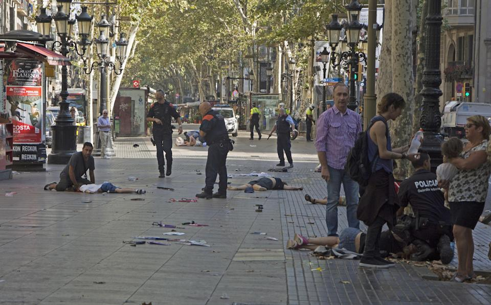 <p>Mossos d'Esquadra Police officers attend injured people after a van crashes into pedestrians in Las Ramblas, downtown Barcelona, northeaster Spain, August 17, 2017. (David Armengou/EFE via ZUMA Press) </p>