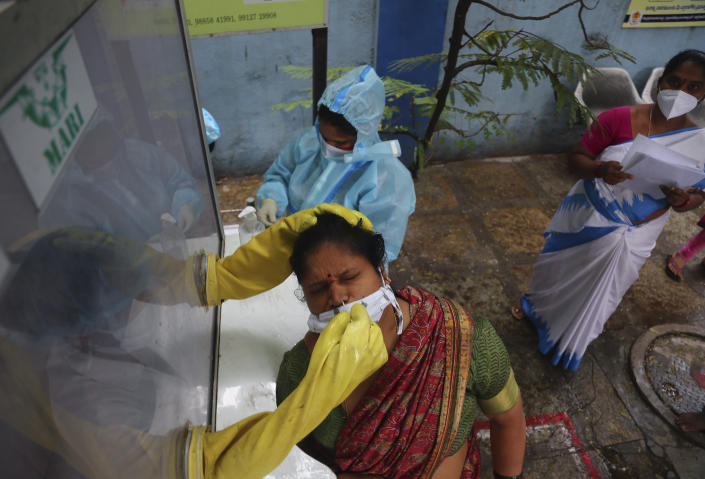 A health worker takes a nasal swab sample at a COVID-19 testing center in Hyderabad, India, Saturday, Nov. 28, 2020. India has more than 9 million cases of coronavirus, second behind the United States. (AP Photo/Mahesh Kumar A.)