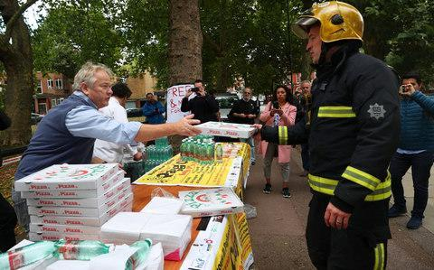 <span>Staff from a local Italian restaurant hand out pizza and water from a stall near Parsons Green station</span> <span>Credit: HANNAH MCKAY/Reuters </span>