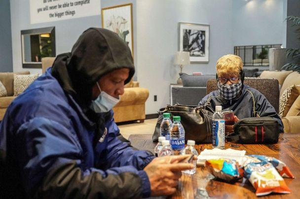 Jason Miszell and his wife Debra Bracey check their smartphones while taking a shelter at Gallery Furniture store which opened its door and transformed into a warming station after winter weather caused electricity blackouts in Houston, Feb. 17, 2021. (Go Nakamura/Reuters)