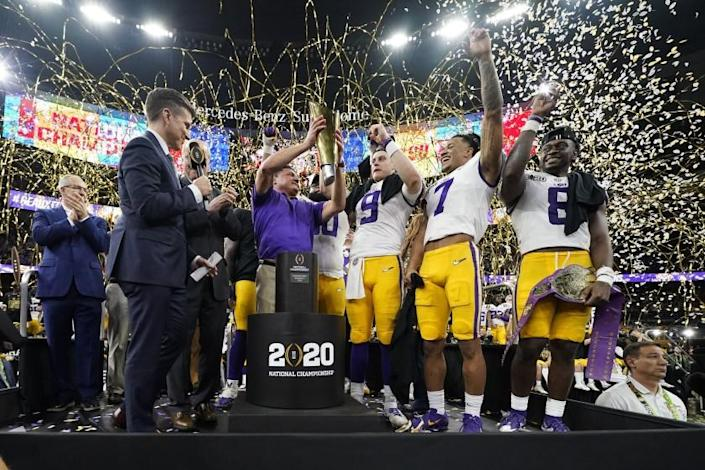 """Louisiana State coach Ed Orgeron holds the title trophy after his team's national championship game win over Clemson in January. <span class=""""copyright"""">(David J. Phillip / Associated Press)</span>"""