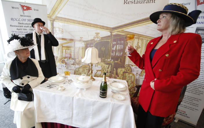 Carmel Bradbam and Andreas Stovic , both at left, from Adelaide, Australia drink champagne as they sit in a mock up of a first class dinning table of the Titanic in the check in area for the MS Balmoral's Titanic memorial cruise in Southampton, England, Sunday, April 8, 2012. Nearly 100 years after the Titanic went down, a cruise with the same number of passengers aboard is setting sail to retrace the ship's voyage, including a visit to the location where it sank. The Titanic Memorial Cruise is set to depart Sunday from Southampton, where the Titanic left on its maiden voyage. The 12-night cruise will commemorate the 100th anniversary of the sinking of the White Star liner. With 1,309 passengers aboard, the MS Balmoral will follow the same route as the Titanic. Organizers are trying to recreate the onboard experience minus the disaster from the food to a band playing music from that era. Organizers said people from 28 countries have booked passage, including relatives of some of the more than 1,500 people who died when the Titanic collided with an iceberg and sank on April 15, 1912. Woman at right declined to be named. (AP Photo/Alastair Grant)
