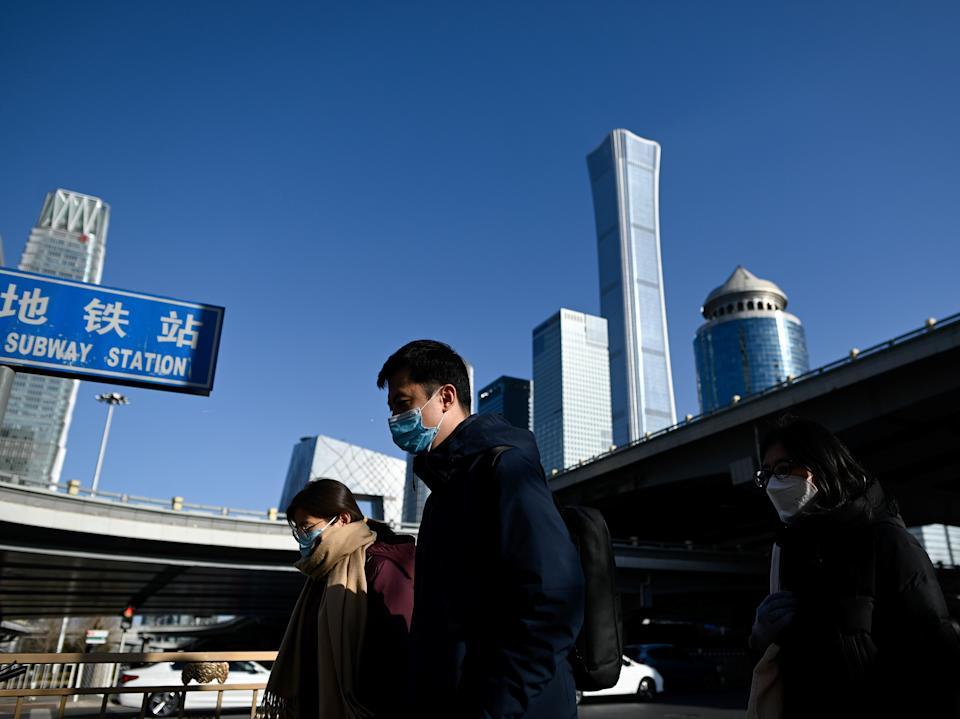 People wearing face masks walk in the central business district of Beijing on Monday (AFP via Getty Images)