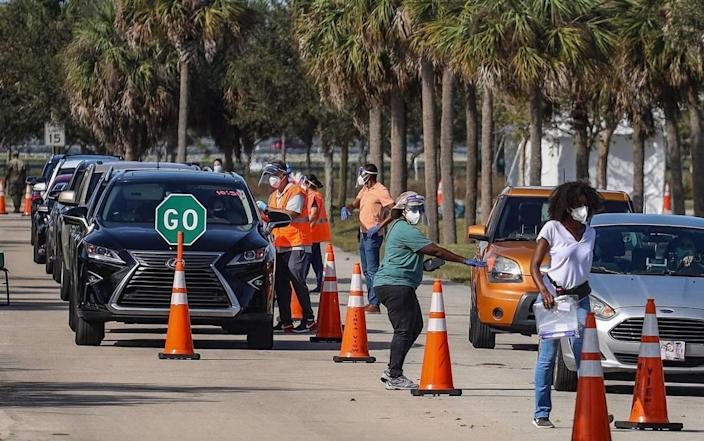 On Sunday, Jan. 3, 2021, motorists line up for COVID-19 vaccination shots for people who are 65 and older as site staffers assist them at Vista View Park in Davie, Florida.