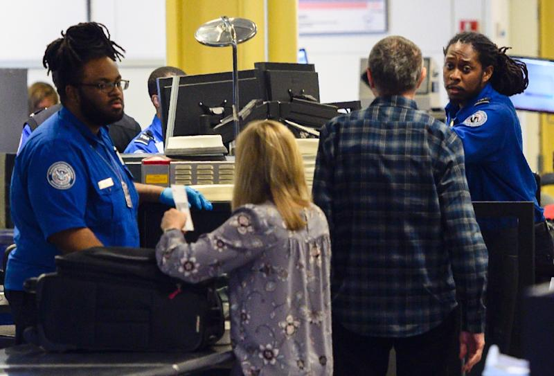 Longer airport inspections due to the government shutdown: Transportation Safety Administration (TSA) agents check passengers at Ronald Reagan Washington National Airport near Washington (AFP Photo/Andrew CABALLERO-REYNOLDS)