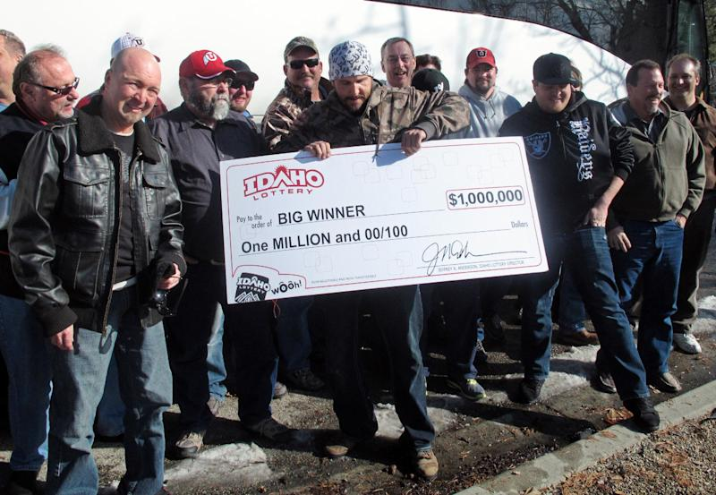 John Polidori, a member of a group of 34 University of Utah maintenance workers who won $1 million in the Idaho Lottery, poses with a ceremonial check on Friday, Feb. 8, 2013 outside the Idaho Lottery offices in Boise, Idaho with other members of the winning group. Another member of his group, which has been playing Idaho's lottery continuously since February 2001, bought the winning ticket in Soda Springs, Idaho. Utah doesn't have a lottery. (AP Photo/John Miller)
