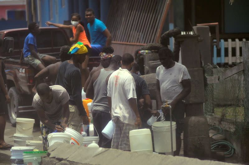 Local residents fill containers of water after a series of eruptions from La Soufriere volcano