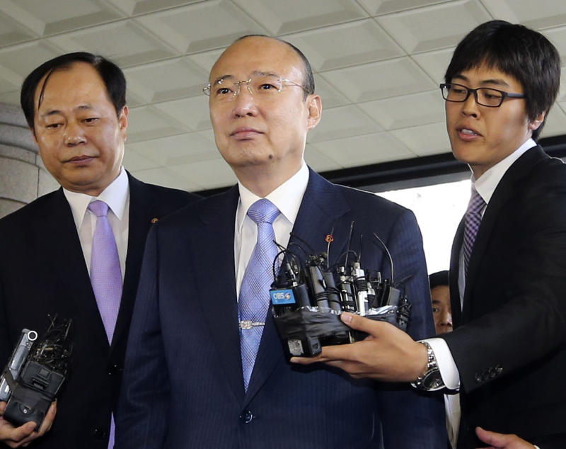 Hanwha Group Chairman Kim Seung-youn, center, arrives at the Seoul Western District Court in Seoul, South Korea, Thursday, Aug. 16, 2102. Kim was sentenced to four years in prison and fined 5.1 billion won ($4.5 million) for embezzlement in a ruling that experts say signals a change in the country's leniency toward chiefs and owners of conglomerates known as chaebol.(AP Photo/Yonhap, Lim Hun-jung)  KOREA OUT