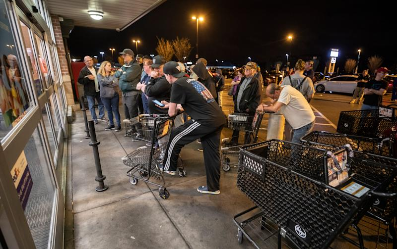 Shoppers grab carts as they wait to enter the Kroger on Breckinridge Lane in Louisville, Ky., as it opens at 7 a.m. March 20. The day before, shoppers rushed the doors.