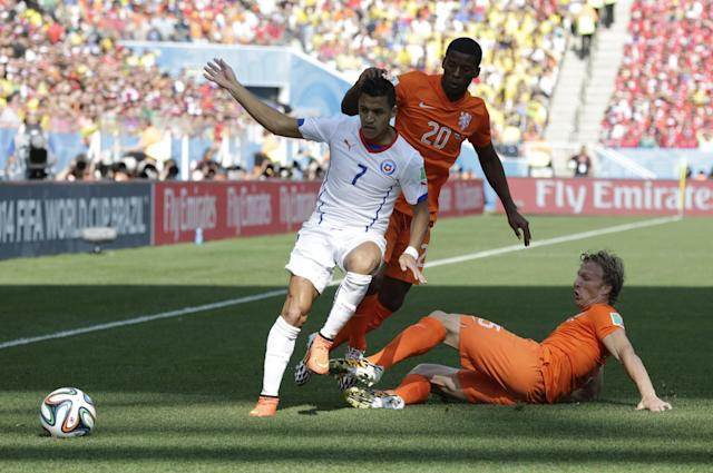 Netherlands' Dirk Kuyt, right, takes the ball off Chile's Alexis Sanchez, left, while Netherlands' Georginio Wijnaldum looks on during the group B World Cup soccer match between the Netherlands and Chile at the Itaquerao Stadium in Sao Paulo, Brazil, Monday, June 23, 2014. (AP Photo/Wong Maye-E)