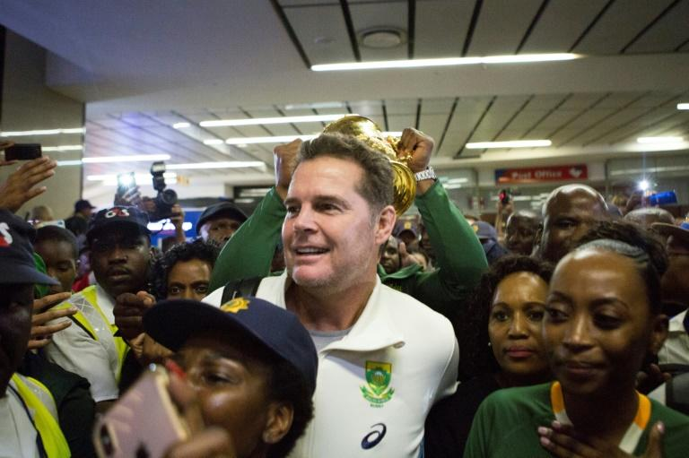 Coach Rassie Erasmus (C) is surrounded by Springbok supporters in Johannesburg after returning from the 2019 Rugby World Cup
