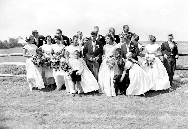 John F. Kennedy, in his first year in the U.S. Senate, and the former Jacqueline Lee Bouvier, described as a 'socialite career girl,' are flanked by their twenty attendants, page boy, and flower girl on their wedding day. (Photo by Pat Candido/NY Daily News Archive via Getty Images)