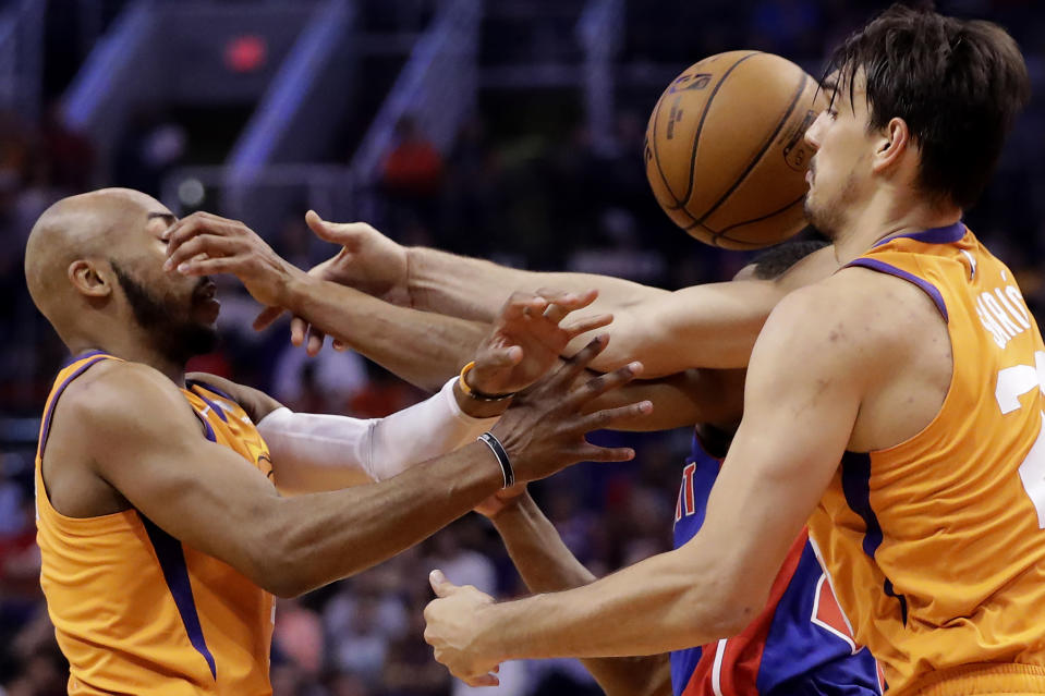 Phoenix Suns guard Jevon Carter, left, forward Dario Saric, right, battle with Detroit Pistons guard Brandon Knight for the loose ball during the first half of an NBA game, Friday, Feb. 28, 2020, in Phoenix. (AP Photo/Matt York)