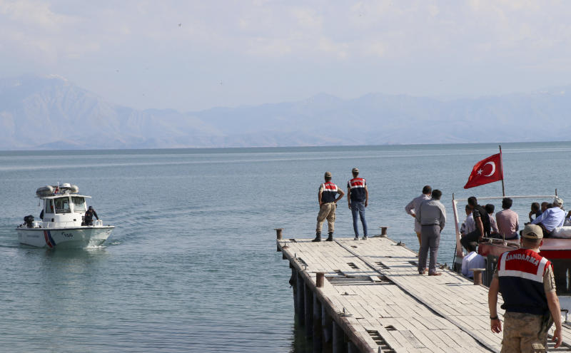 A paramilitary boat searches for people in Lake Van, in eastern Turkey, Wednesday, July 1, 2020. Up to 60 migrants may have been trapped in a boat that sank in the lake last week, Turkey's Interior Minister Suleyman Soylu said Wednesday. Turkey launched a search-and-rescue mission involving helicopters and boats after the boat carrying migrants across Lake Van was reported missing on June 27. (DHA via AP)