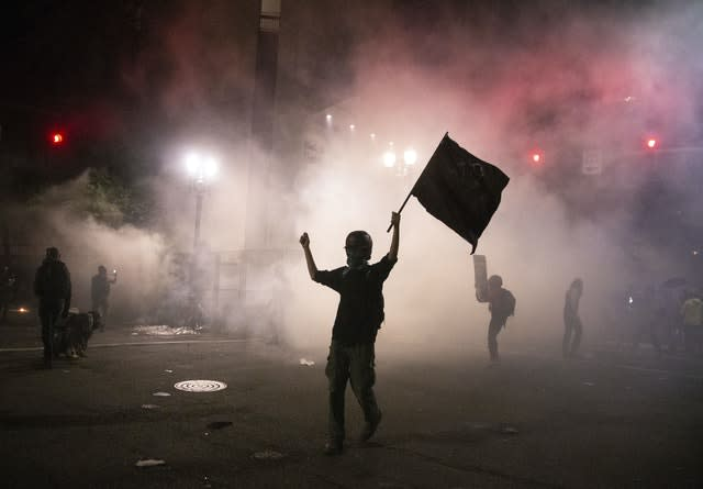Tear gas is released during late night protests in Portland