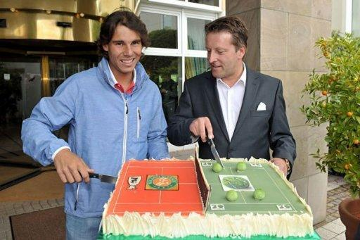 Rafael Nadal (L) and Gerry Weber tournament director Ralf Weber cut a cake upon Nadal's arrival